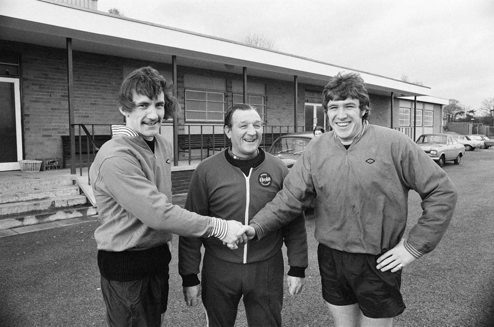 Emlyn Hughes, right, and Bob Paisley welcome new player Terry McDermott, November 1974