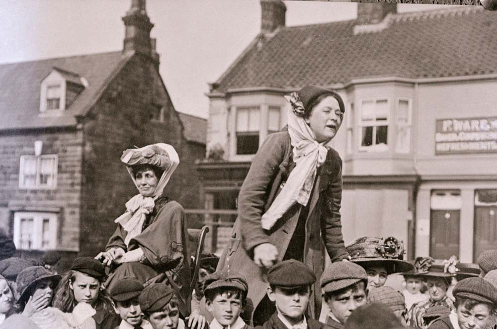 Emmeline Pankhurst sits while fellow suffragette Margaret Bondfield makes a speech, January 1910