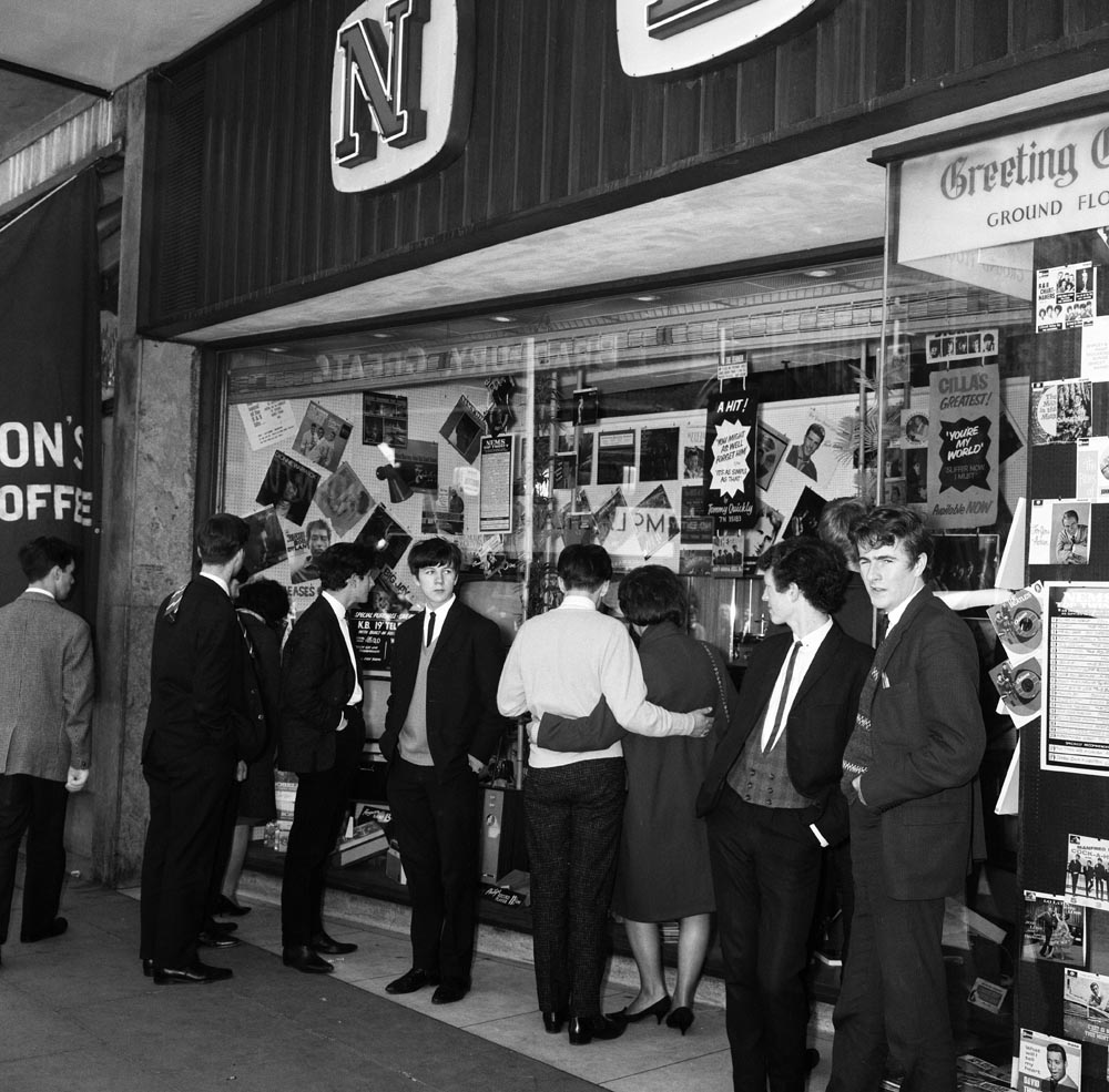 Youngsters mill around the NEMS music shop owned by Brian Epstein, June 1964