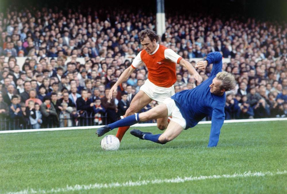 Man United's Denis Law tackles Arsenal defender