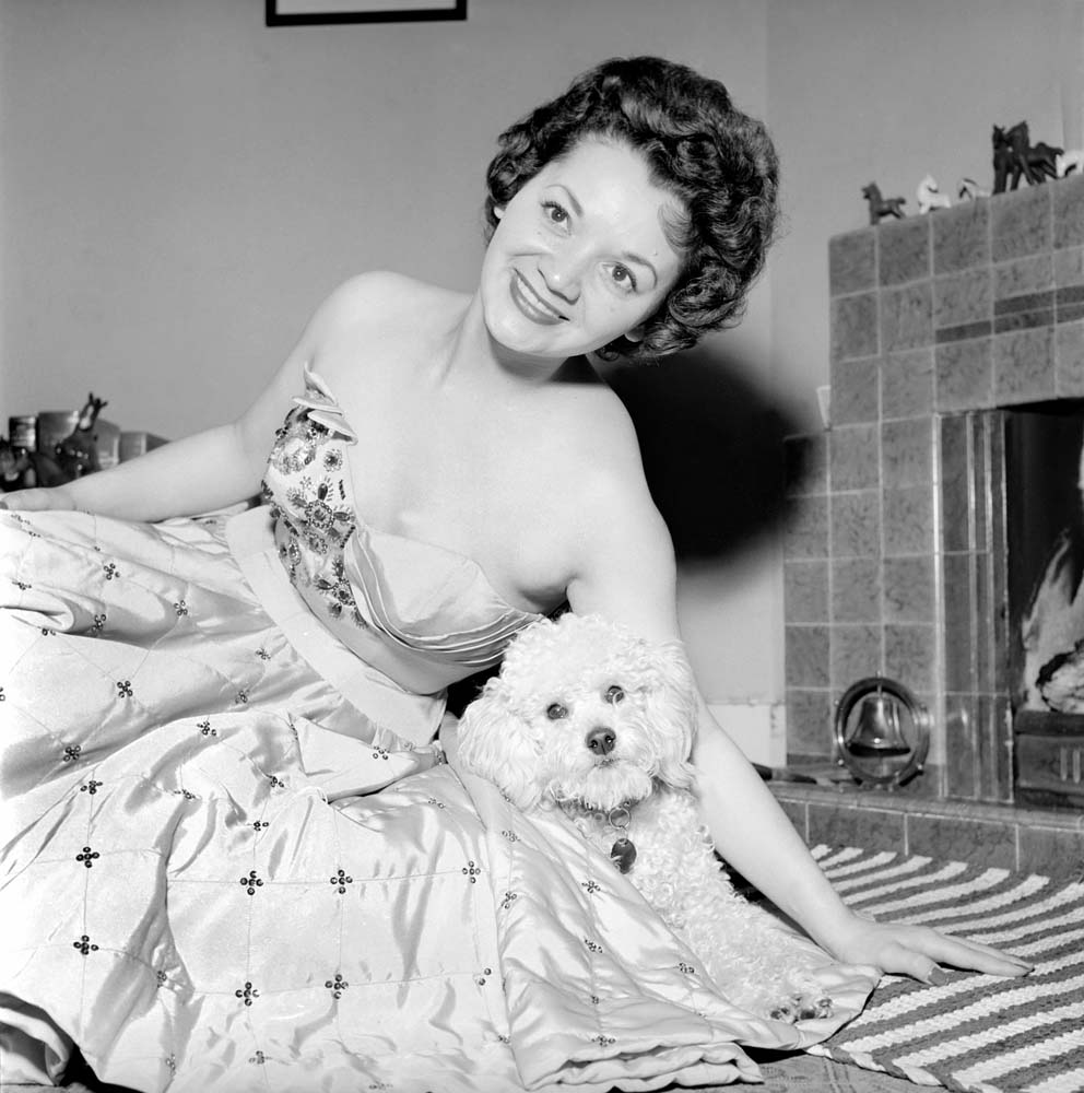 Lita Roza relaxes at home with her pet dog, January 1957