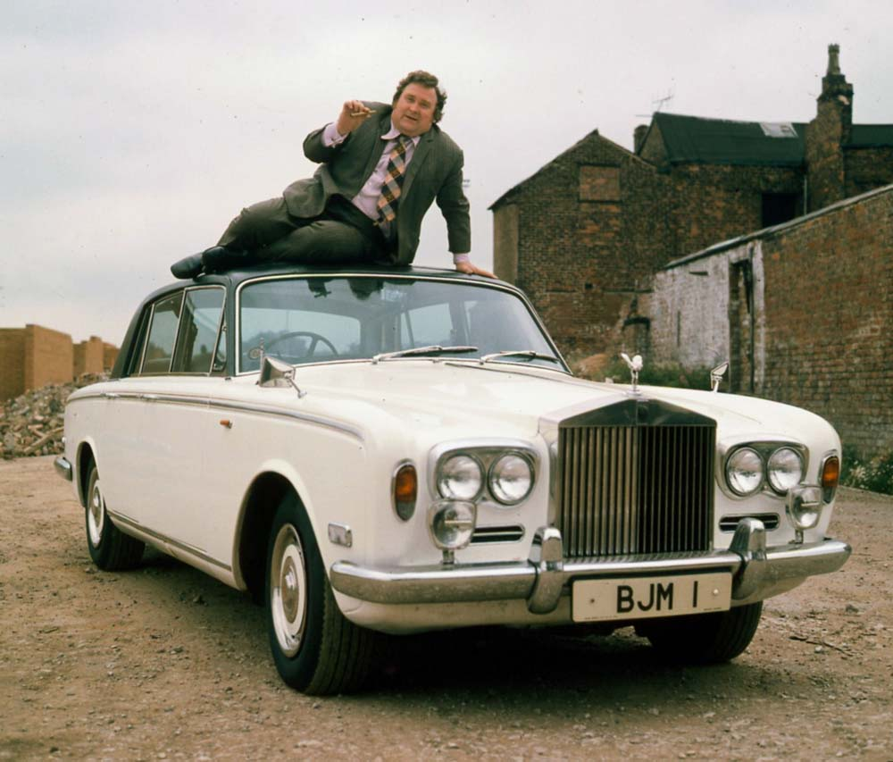 Bernard Manning poses on the roof of his Rolls Royce, April 1981