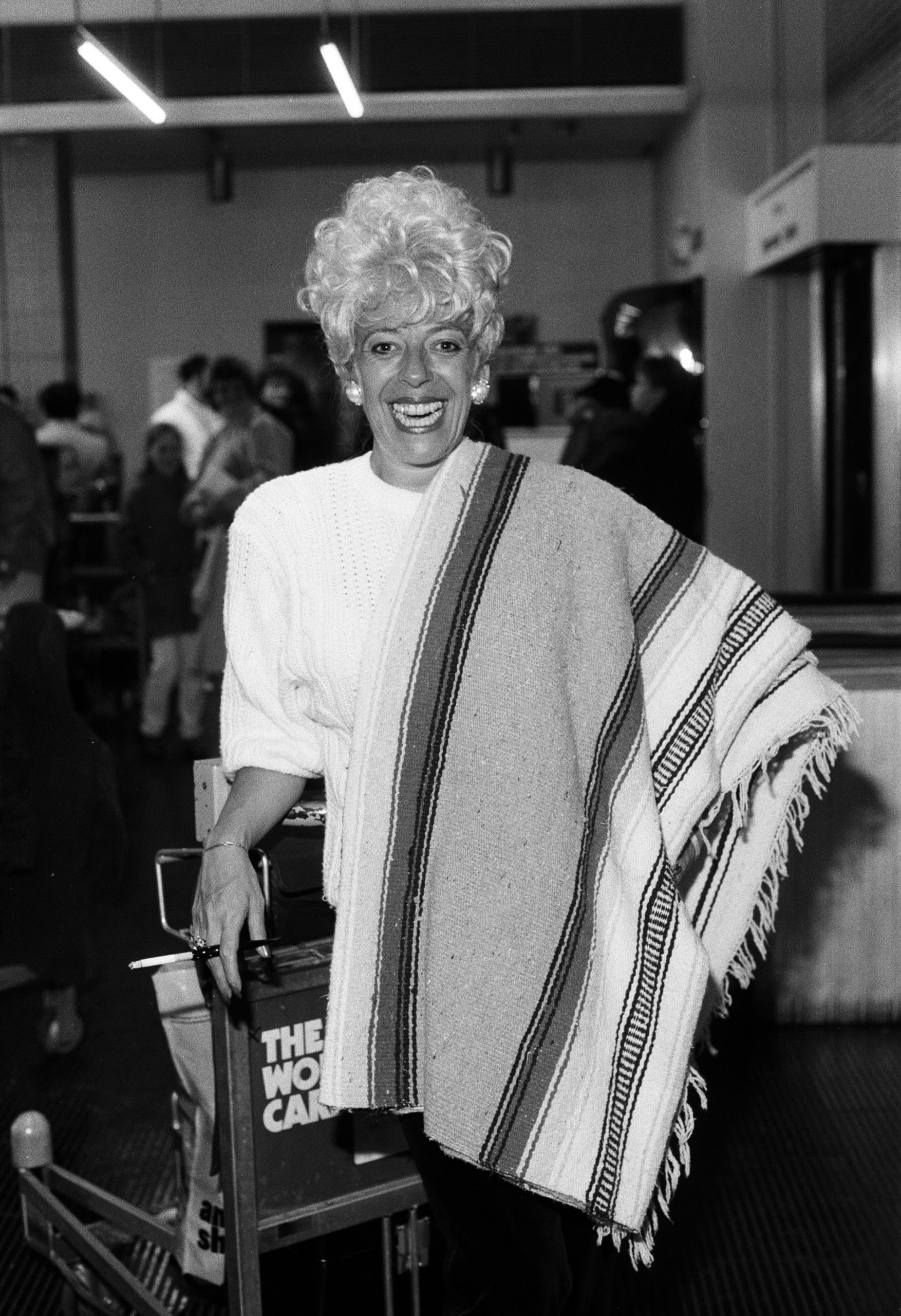 Julie Goodyear breezes into Manchester Airport ready to film