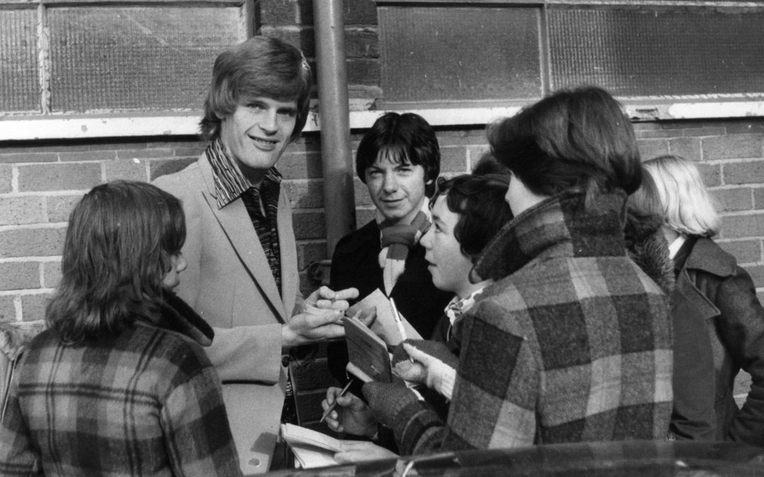 Pictured: Gordon McQueen signs autographs for young fans outside Old Trafford.