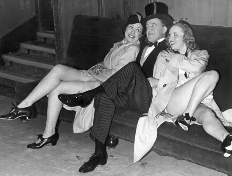 Backstage with ITMA - Tommy Handley and two members of the chorus line, February 1940