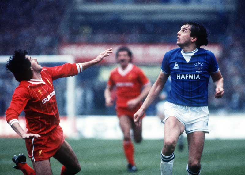 Graeme Sharpe of Everton watches a high ball with Liverpool's Mark Lawrenson, March 1984