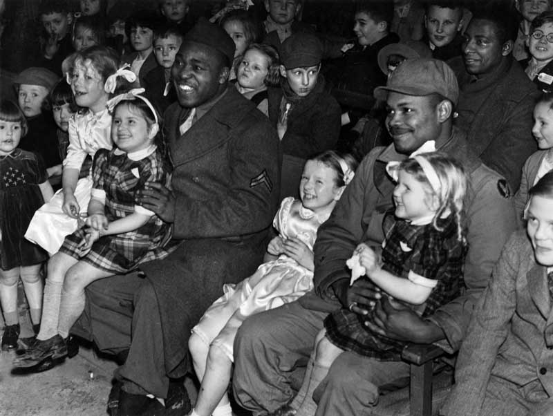 American troops stationed in the UK treat children to a cinema trip, December 1943