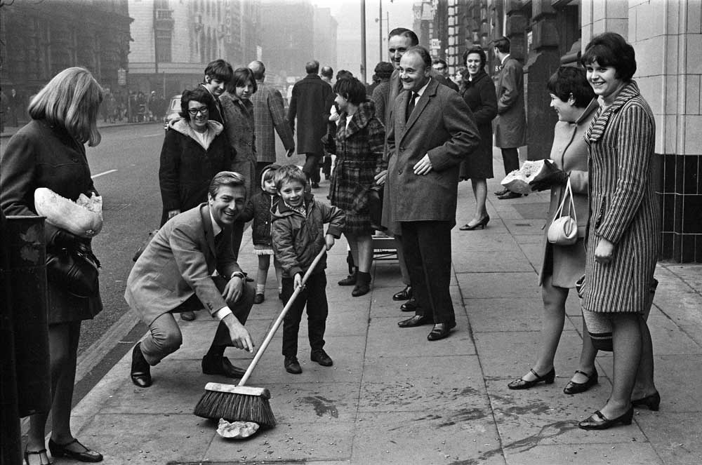 Volunteers help Des O'Connor clean up the pumpkin he dropped outside the Palace Theatre, November 1967