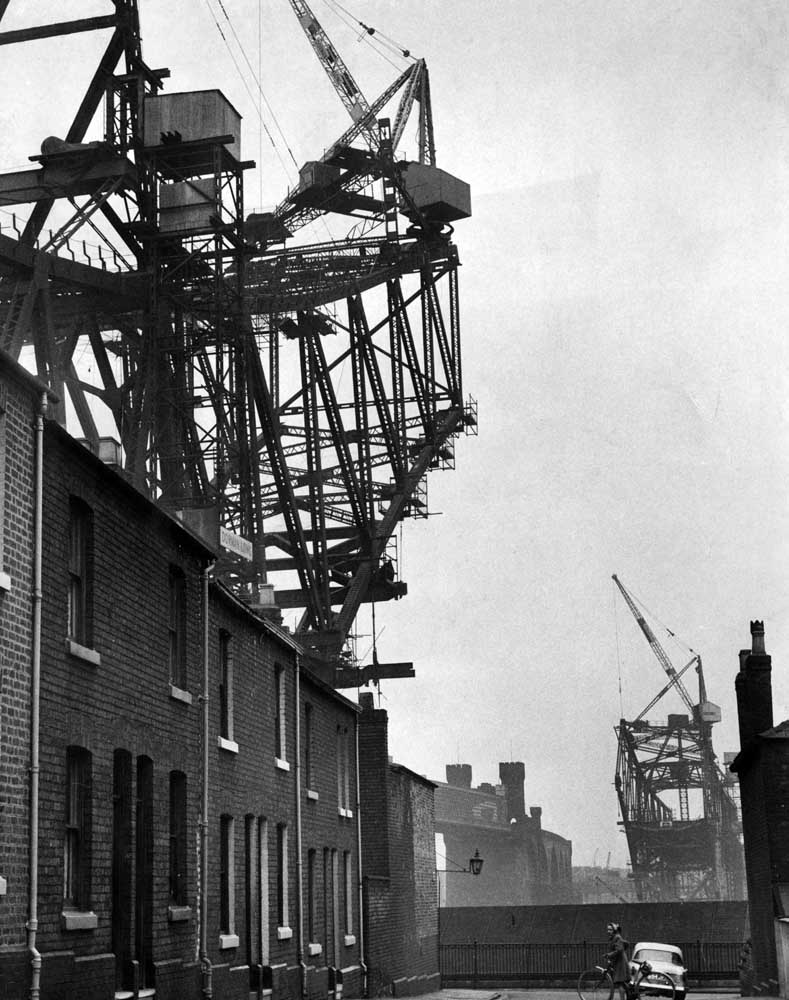 Houses in Runcorn are dwarfed by the new Runcorn-Widnes bridge, which is under construction. 19th March 1960.