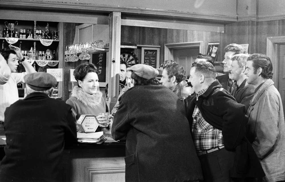 Emily Nugent (Eileen Derbyshire) serving a lively crowd in the Rovers, April 1968