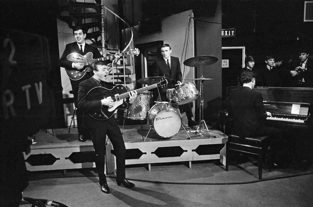 John Lennon on Ready Steady Go! with Paul McCartney being interviewed in the background, March 1964