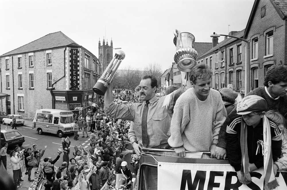 Bruce Grobbelaar holds up two trophies in Liverpool's league and cup double parade, May 1986