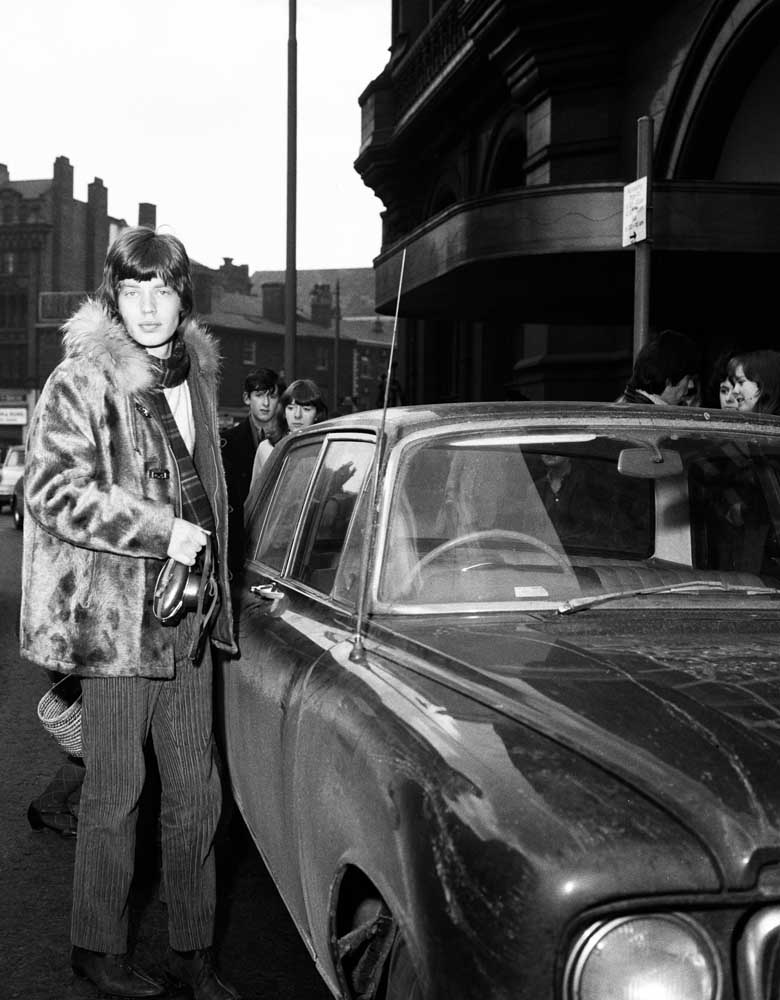 Mick Jagger climbs into his car after filming in Manchester, March 1965