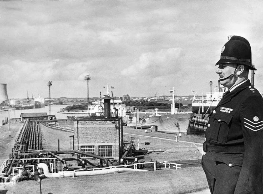 Sergeant Jim Roper surveying Stanlow Island, situated on The Manchester Ship Canal, North West England. 2nd April 1976