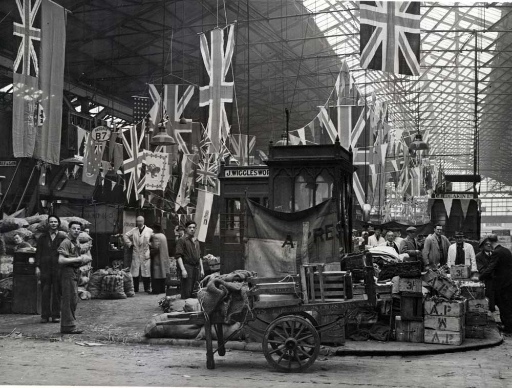 Flags of many nations draped in a Manchester marketplace on VE Day, May 1945