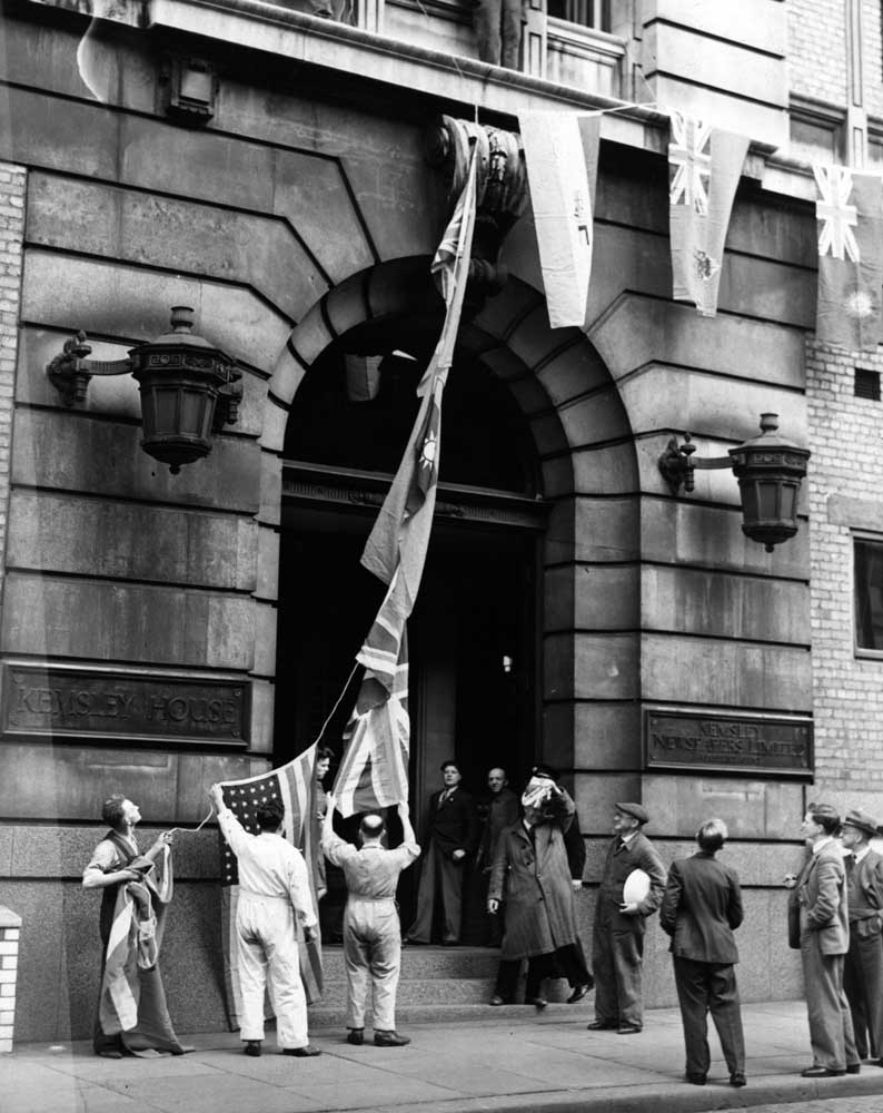 Hoisting flags outside Kemsley House print works on VE Day, May 1945