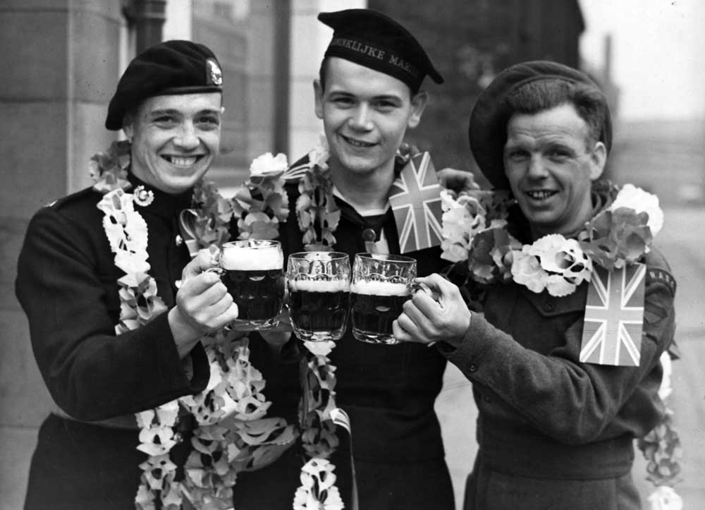 Three servicemen enjoy well-earned pints on VE Day, May 1945