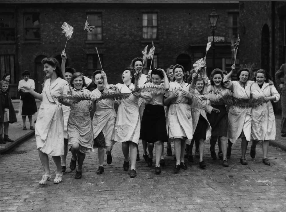 Women workers celebrate outside a Manchester factory, May 1945