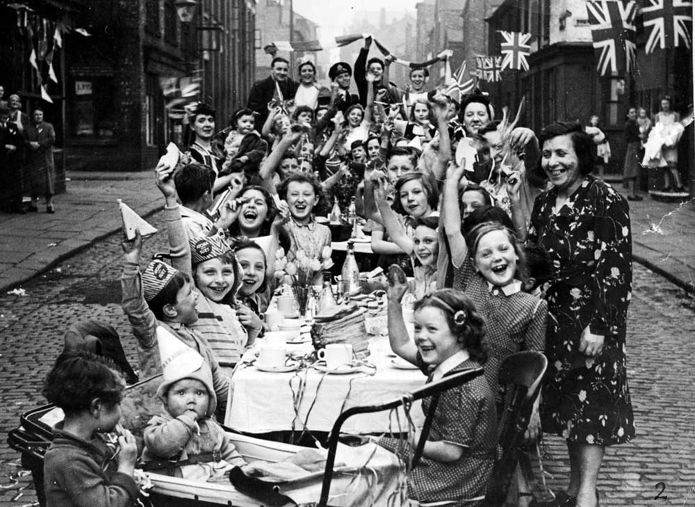 Around 50 children sit down to tea and cakes at a street party, May 1945