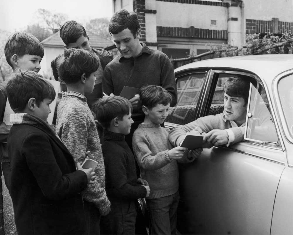 Everton midfielder Colin Harvey, standing, signing autographs with Howard Kendall, April 1968