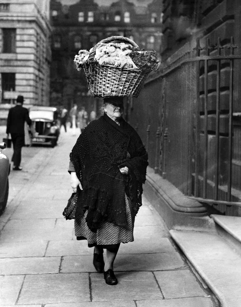 A wartime stallholder carrying flowers to market on her head, November 1945