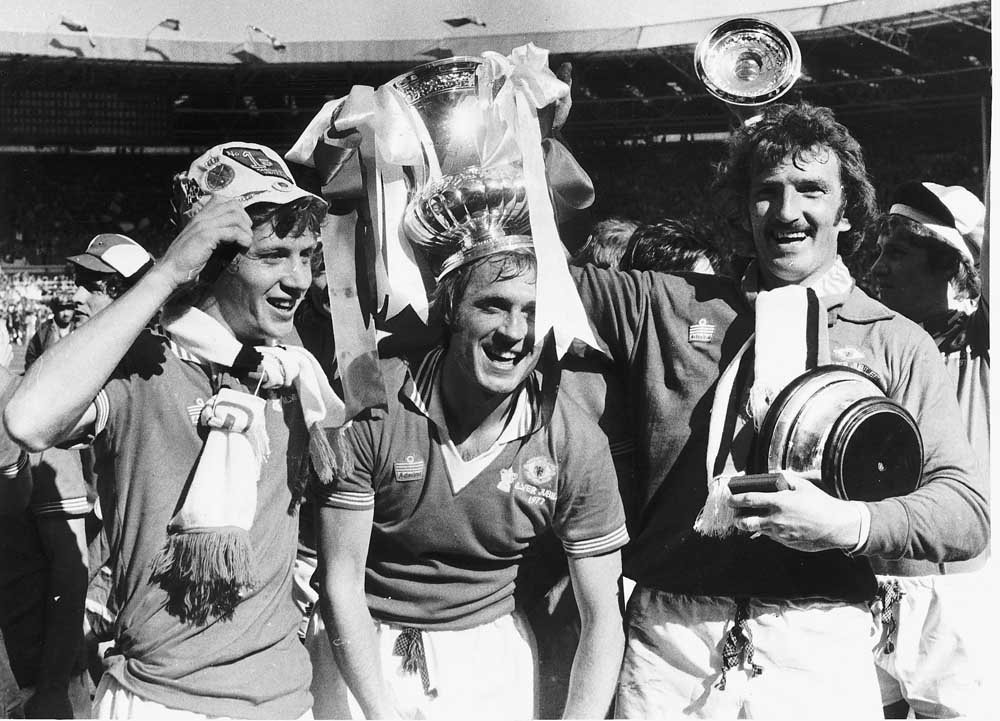 Manchester United players Jimmy Nicholl, Jimmy Greenhoff and Alex Stepney celebrate winning the win FA Cup against Liverpool, May 1977