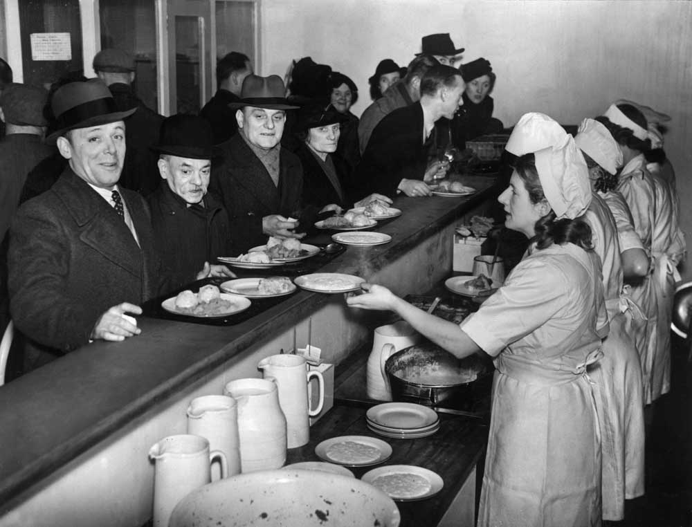 Civilians queue expectantly at an emergency feeding centre in Manchester, February 1941