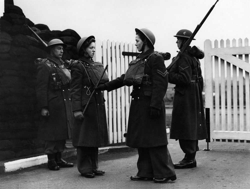 Changing of the guard at a mixed anti-aircraft gun emplacement at Prestwich, April 1942