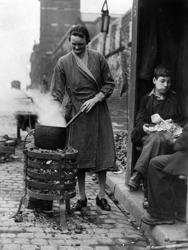 Cooking on a watchman's brazier during a gas strike in Manchester, April 1944