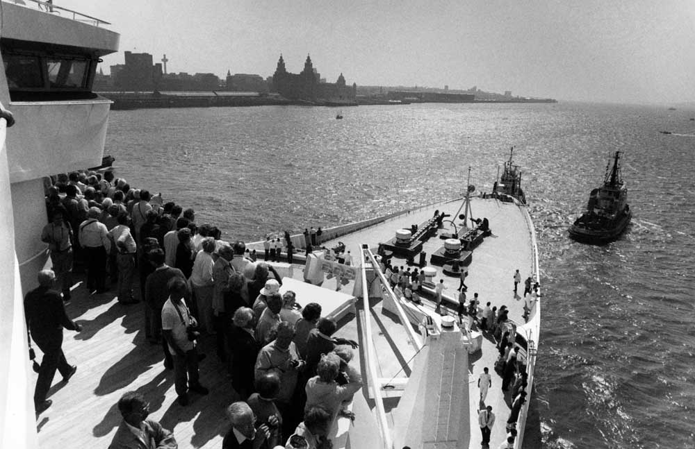 Passengers on the bow of the QE2 with the Liverpool waterfront in the distance, July 1990