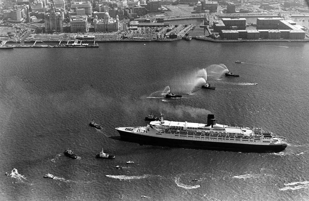 Tug boats welcome the QE2 to Pier Head, July 1990