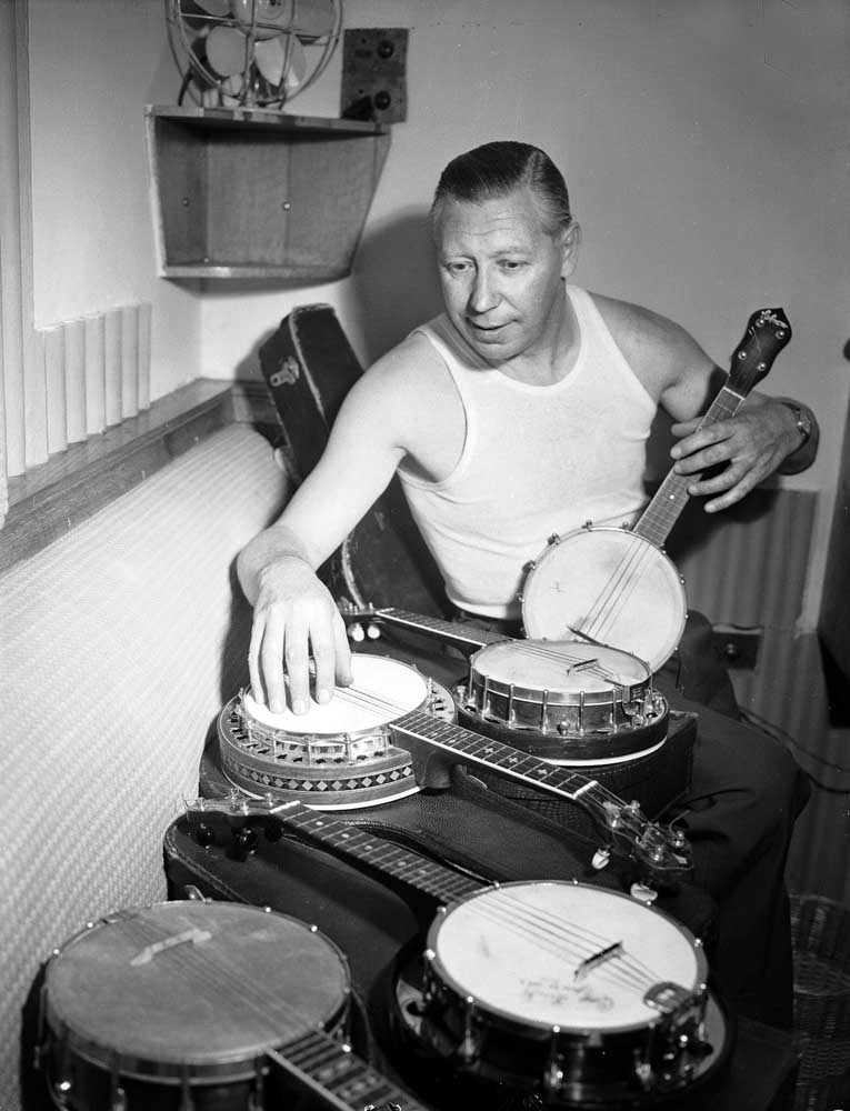 George Formby with a selection of his banjo ukuleles, January 1953