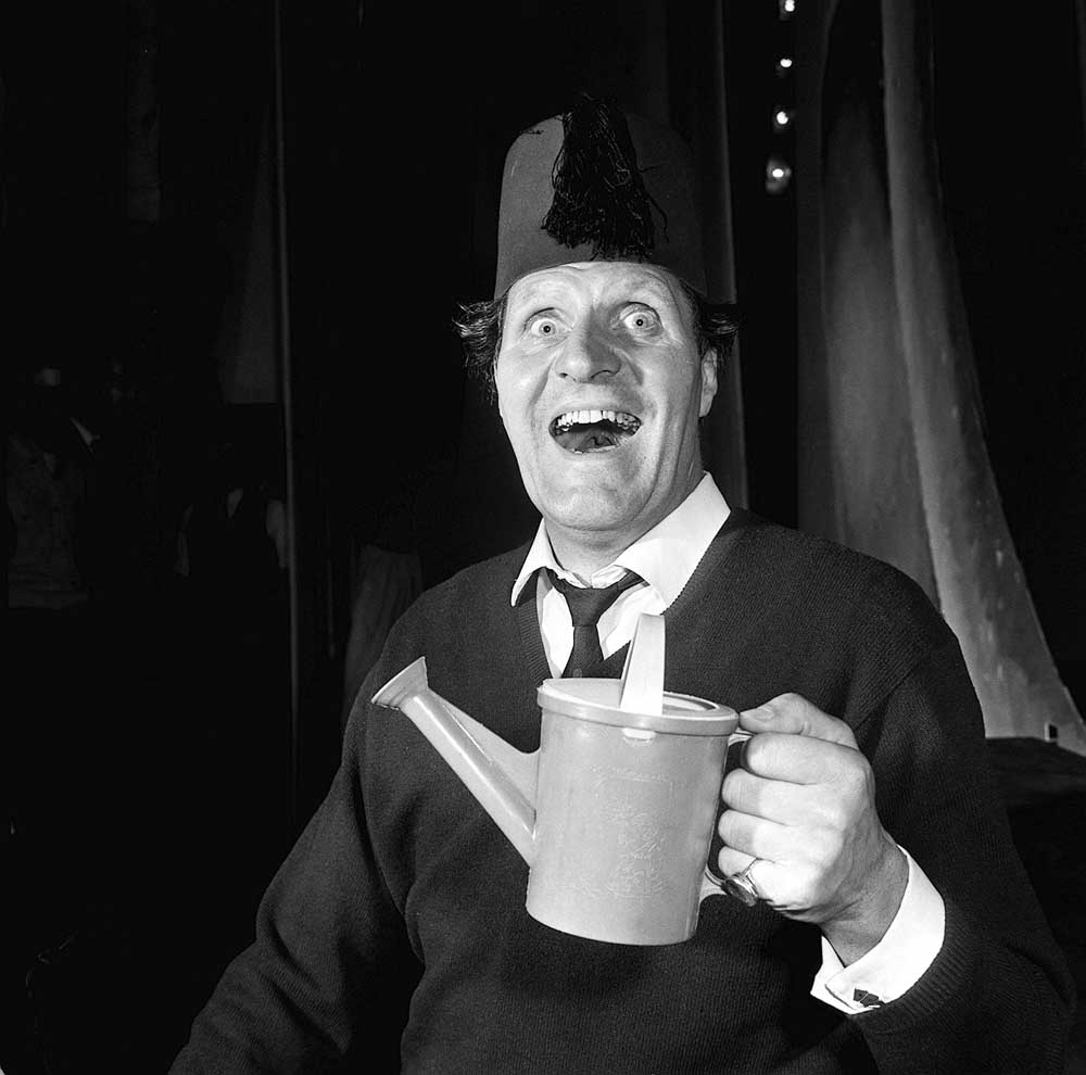 Tommy Cooper in trademark fez performing his comedy-magic act, June 1965