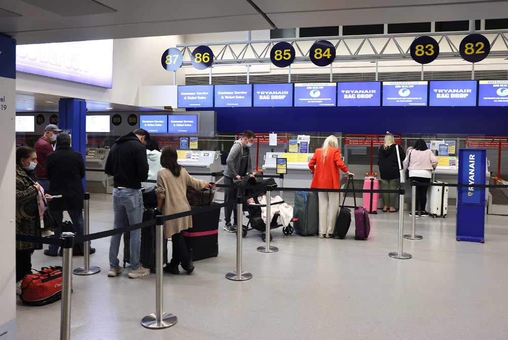 Queues of passengers at the check-in counter at Manchester Airport, ready to board one of the first flights to Portugal